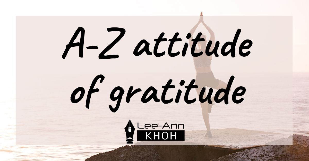 Text reads: A-Z attitude of gratitude. Background contains a person practising yoga on a rock overlooking the ocean.