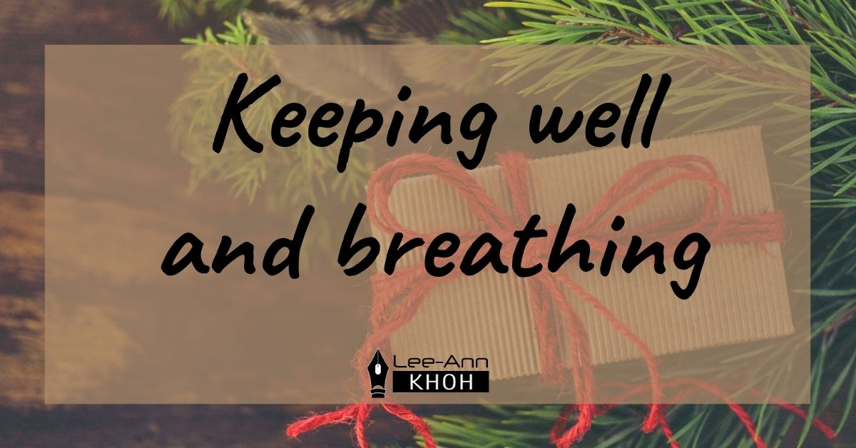 Text reads: Keeping well and breathing. Background contains cardboard gift box and close-up of Christmas tree.