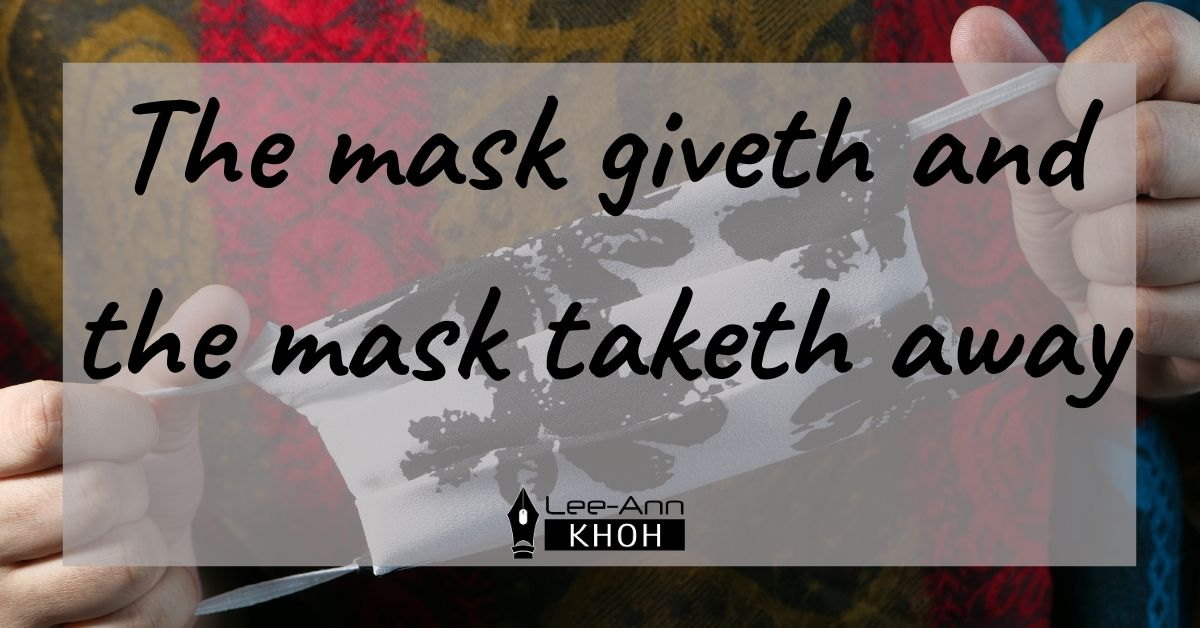 Text reads: The mask giveth and the mask taketh away. Background contains someone holding a cloth face mask.