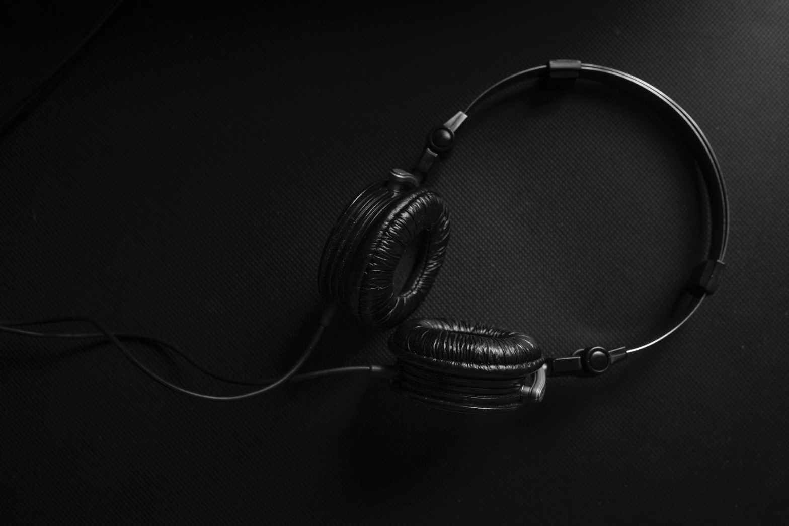 Black headphones on a black surface.