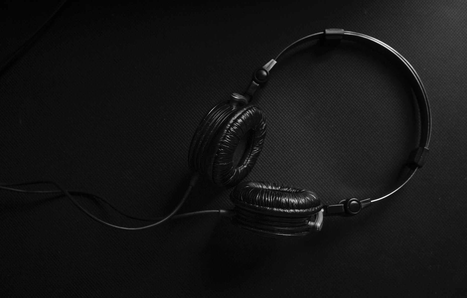Black headphones on a black surface.
