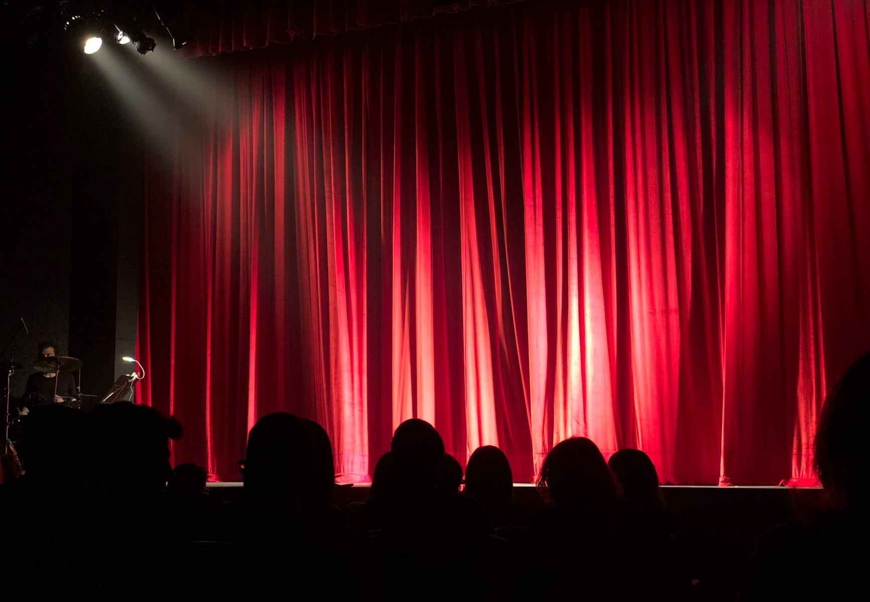 Silhouettes of people at the theatre with curtains closed.