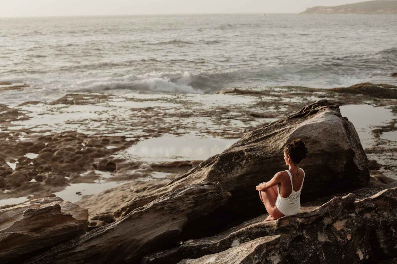 A woman sits on a rock, looking out towards the ocean.