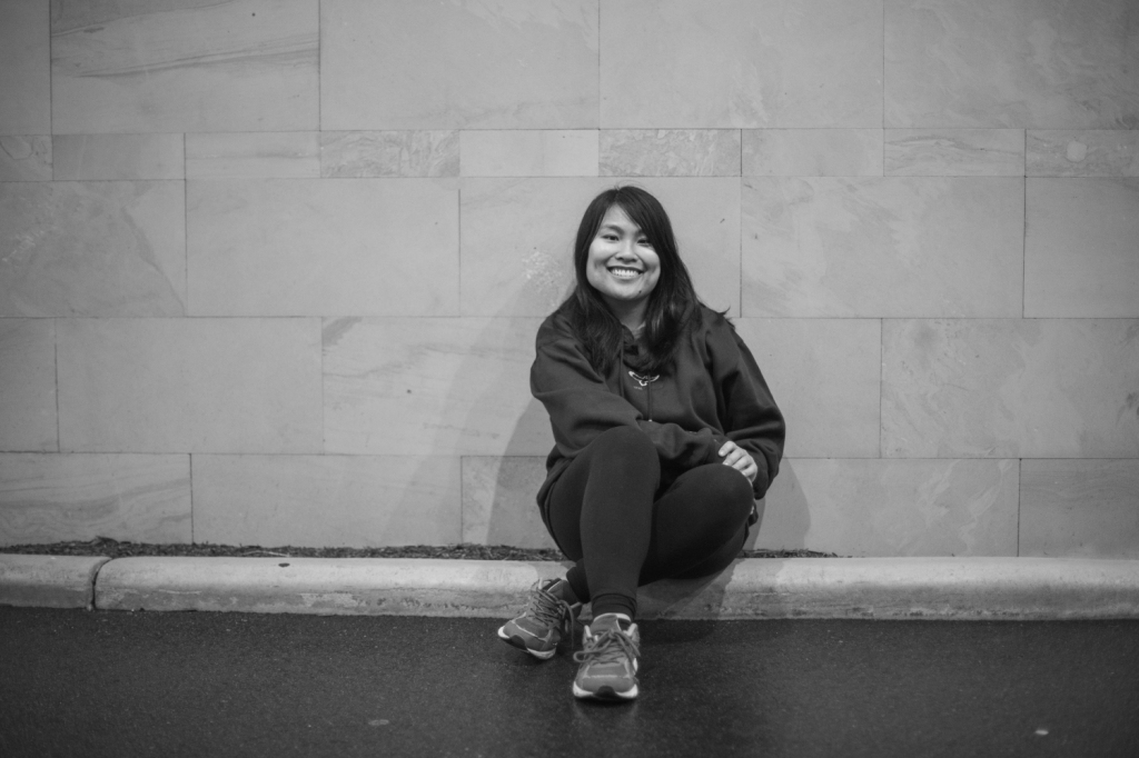 Black and white photo of Lee-Ann sitting cross-legged on a kerb in front of a wall.