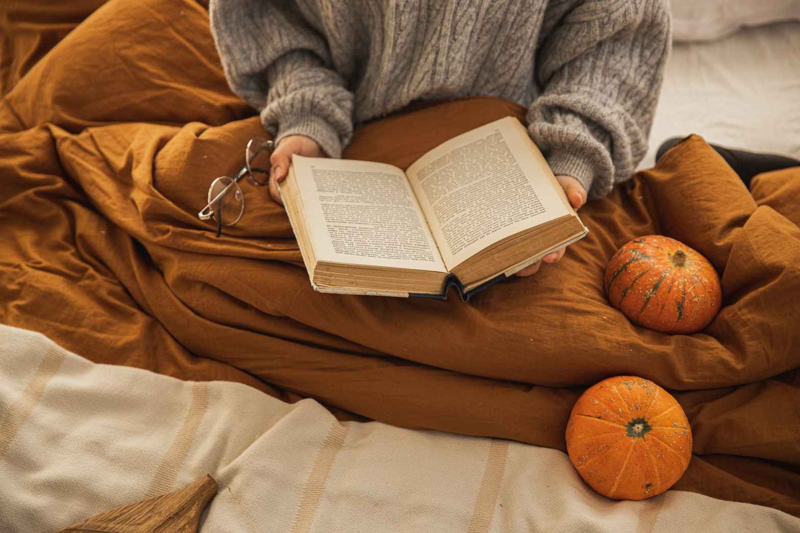 Someone reads a book in bed, with 2 pumpkins beside them.