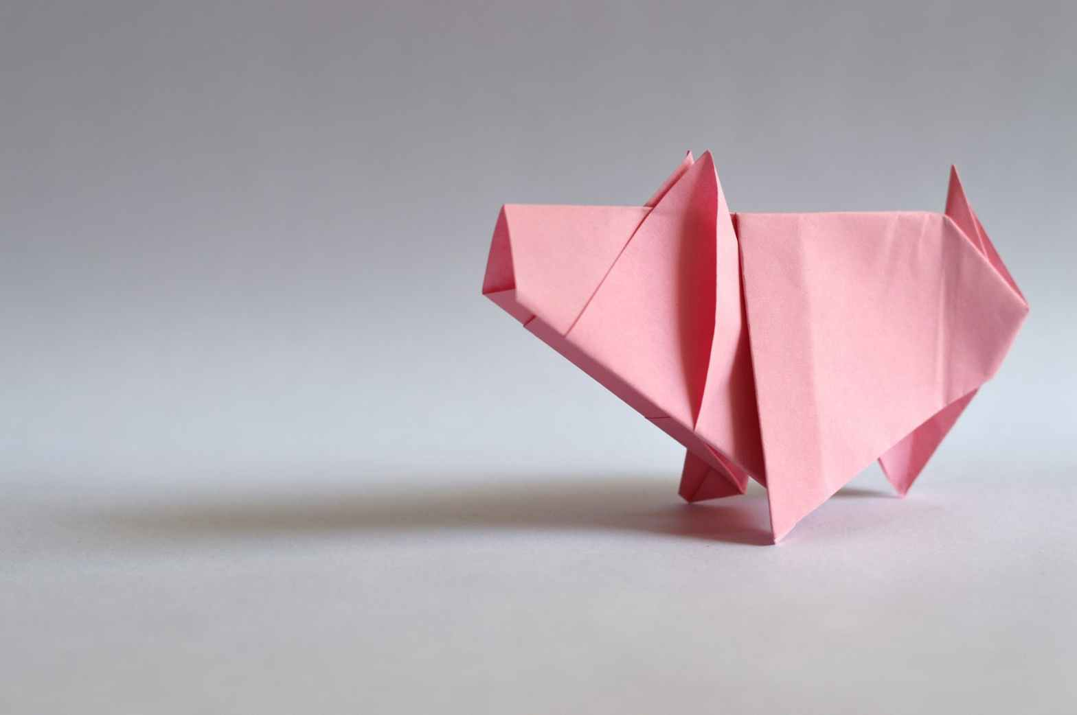 Origami pig folded with pink paper.